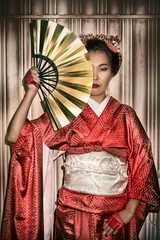 Asian woman in traditional red Kimono holding a paper fan, which covers half of her face.
