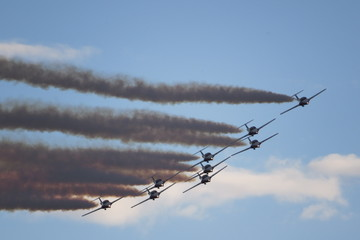Free public event: Acrobatic aircraft in formation with trails in Quebec, Canada.
