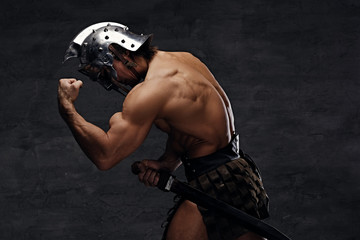 Shirtless athletic male in silver gladiator helmet.