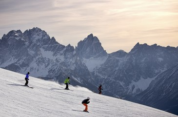Skiers at the Elmo Mount ski area, Sesto Dolomites in the background, South Tyrol, Italy