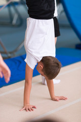 boy stands on his hands in the gym