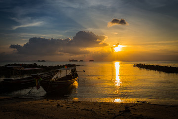 The yellow setting sun sets over the horizon at sea. On the shore there are boats. thailand.