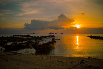 Sunset. On the beach there are boats. Thailand.