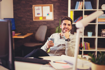 Creative businessman listening music at desk in office, and drinking coffee
