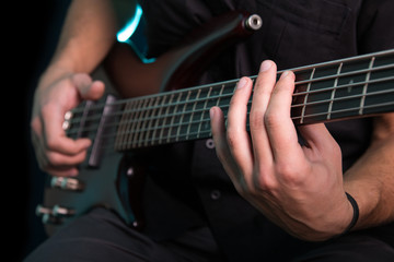 Young man playing electric guitar on dark background
