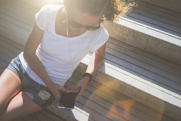 View from above. Sunny summer day, the girl in sunglasses, white T-shirt and denim shorts sitting on the stone steps and listening to music, while holding a smartphone.