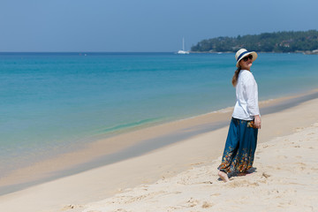 Girl in a hat and dress walking on the beach in Thailand
