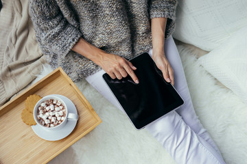 Top view, close-up of tablet computer with blank screen in female hands. Girl sitting and using a tablet computer. Nearby is a wooden tray with a cup of cocoa with marshmallows and cookies. Mock up.