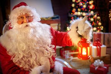 happy Santa Claus sitting near Christmas tree