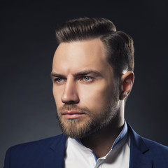 Close-up portrait of young man with perfect hair and short beard over dark background