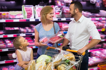 parents with daughter choosing meat in refrigerated section in h
