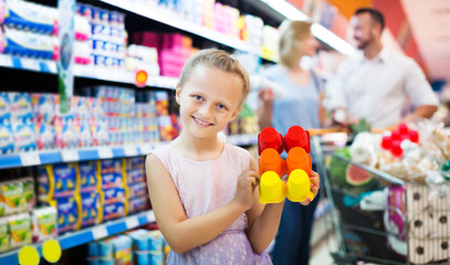 Girl holding package with yogurt