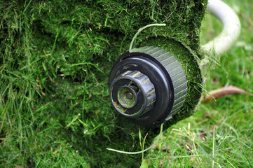 Part of the electric spit with a thread and a protective casing covered with cut grass. Close up.