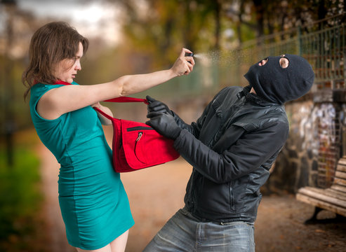 Self defense concept. Young woman was attacked by man in balaclava.