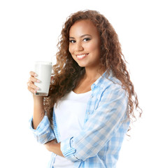 Beautiful young African-American woman drinking milk on a white background
