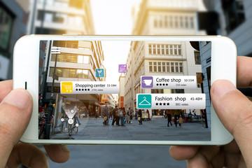 Augmented reality marketing concept. Hand holding smart phone use AR application to check relevant information about the spaces around customer. City and flare light background Wall mural