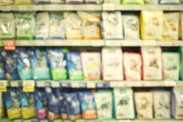 Blurred view of packs with animal food on pet shop shelves