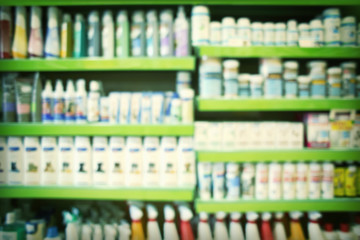 Blurred view of animal shampoos, vitamins and other goods on pet shop shelves
