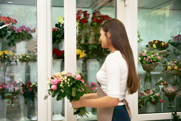 Pretty young florist with bouquet near flower shop