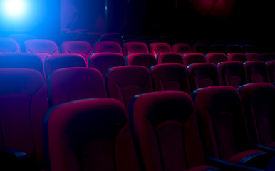 Dark film theater with projection light and empty seats