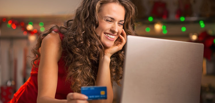 Woman with credit card choosing Christmas gifts on laptop