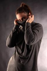 Frau im grauen Rollkragenpullover versteckt sich schüchtern