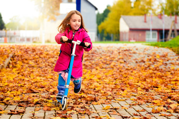 Girl in pink coat is riding scooter on maple leaves.