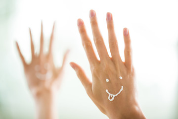 Closeup woman beautiful hands with long fingers applying moisturising and soothing cream on skin. Funny smiling faces, emoji.
