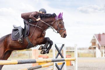 Young rider girl at show jumping. Jump hurdle