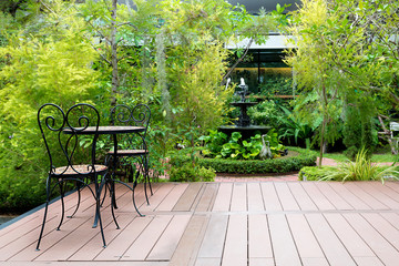 Black chair in wood patio at green garden with fountain in house