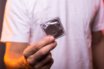 Unknown man in white shirt holding condom in hand