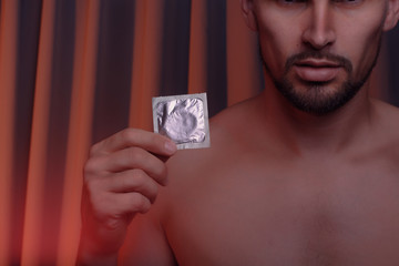 Cropped shot of young man holding condom