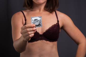 Sexy woman in lingerie holding condom in hand