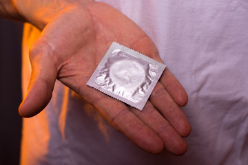 Sexual contraception: male hand with condom