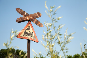 Very old rusty road sign with a train picture - railroad crossing