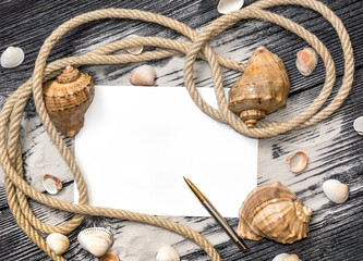 Frame of seashells with rope, sand and empty sheet.