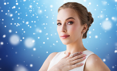 woman in white dress with diamond jewelry and snow
