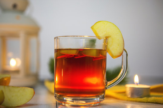 Чай в стеклянной кружке с долькой яблока и кусочками яблока на белом столе. Стол украшен свечами, яблоками, еловой веткой, желтой салфеткой и фонарем со свечой