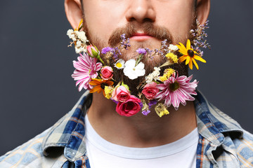 Handsome man with beard of flowers on dark background