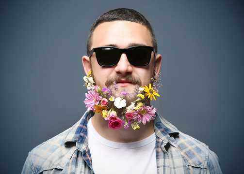 Handsome man in sunglasses with beard of flowers on dark background