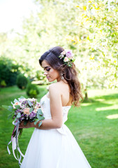 Beautiful young bride with a bouquet of wedding flowers. Holiday