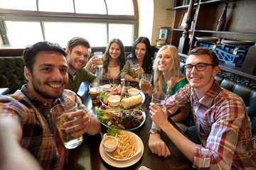 happy friends taking selfie at bar or pub
