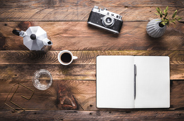 Artist, hipster, photographer table with black notebook, camera, coffee maker and cup of espresso. Flat lay. View from above, copy space.