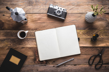 writer, photographer, artist, hipster wooden rustic desk with black notebook, camera, coffee maker and cup of espresso. Flat lay. View from above, copy space.