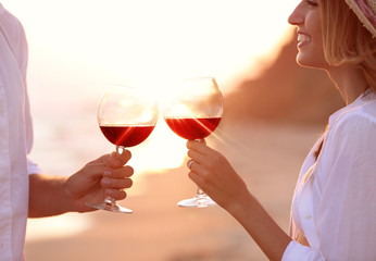 Young happy couple drinking red wine on seashore, closeup