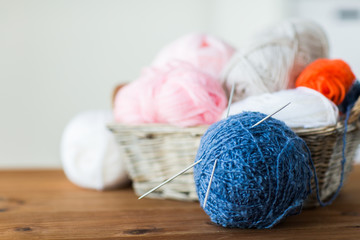 basket with knitting needles and balls of yarn