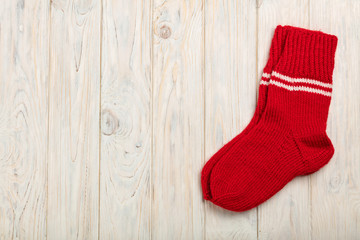 Knitted wool socks in red on a light wooden background.