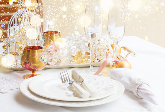 Tableware for christmas - set of plates, cups and utencils with white table cloth and christmas golden decorations with bokeh lights