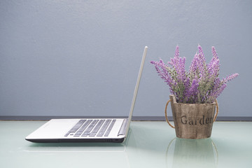 Office table with violet flower on pot.