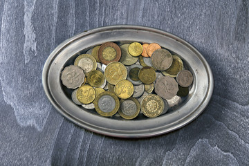 heap of different coins on a silver platter
